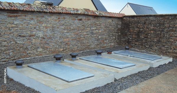 trois ossuaires posés côte-à-côte le long d'un mur. Stradal