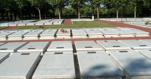 Terres communes du cimetière avec des caveaux aux dalles de béton blanc, allées rouges et présence végétale. Fabricant Stradal